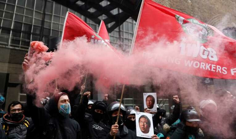 Deliveroo riders set off flares outside company's London HQ in strike over pay and conditions